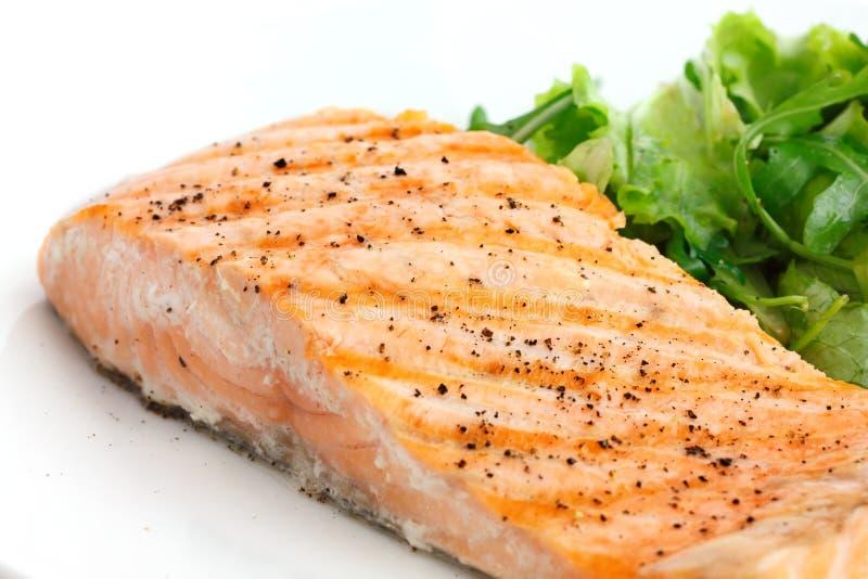 Ψημένη στη σχάρα λωρίδα του σολομού στο πιάτο με την πράσινη σαλάτα στοκ φωτογραφία με δικαίωμα ελεύθερης χρήσης