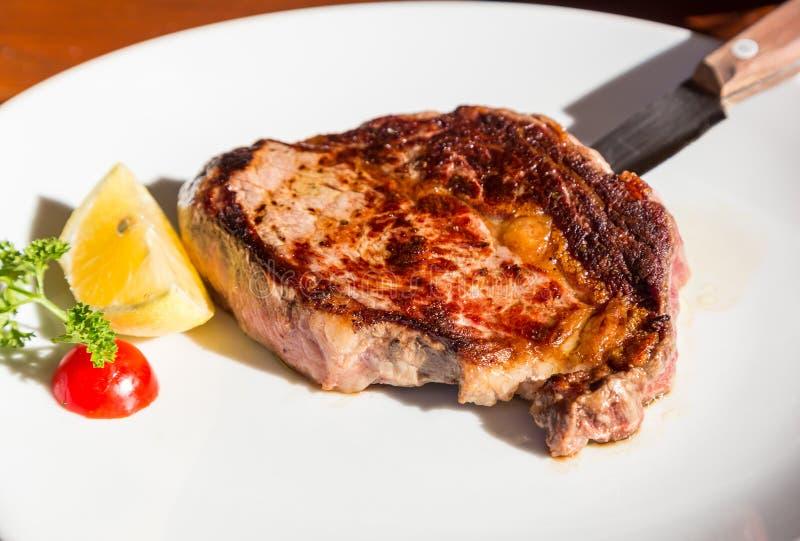 Ψημένη στη σχάρα ribeye μπριζόλα με το μαχαίρι στο εστιατόριο στοκ εικόνες
