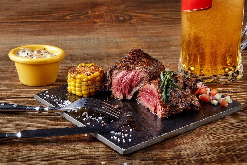 Ψημένη στη σχάρα tenderloin μπριζόλα roastbeef και σάλτσα μανιταριών στο μαύρους τέμνοντες πίνακα και το ποτήρι της μπύρας στο ξύ στοκ φωτογραφίες