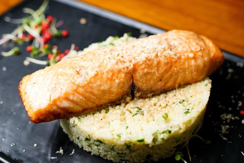 Ψημένος στη σχάρα σολομός με τα gras, το κουσκούς και το αγγούρι συκωτιού foie στο άσπρο ρύζι στοκ εικόνες
