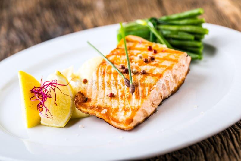 ψημένος στη σχάρα σολομός Λωρίδα σολομών με το λεμόνι και τα πράσινα φασόλια ψάρια που ψήνονται στη σχάρ&alp στοκ εικόνες με δικαίωμα ελεύθερης χρήσης