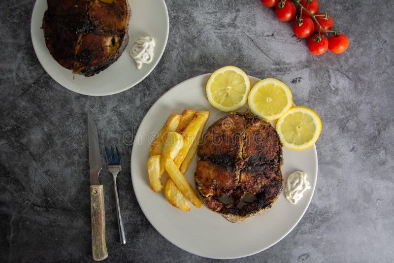 Ψημένος στη σχάρα τόνος με το σκόρδο, το λεμόνι, τις ντομάτες κερασιών, τα τσιπ πατατών και τη σάλτσα ταρτάρου στοκ εικόνες