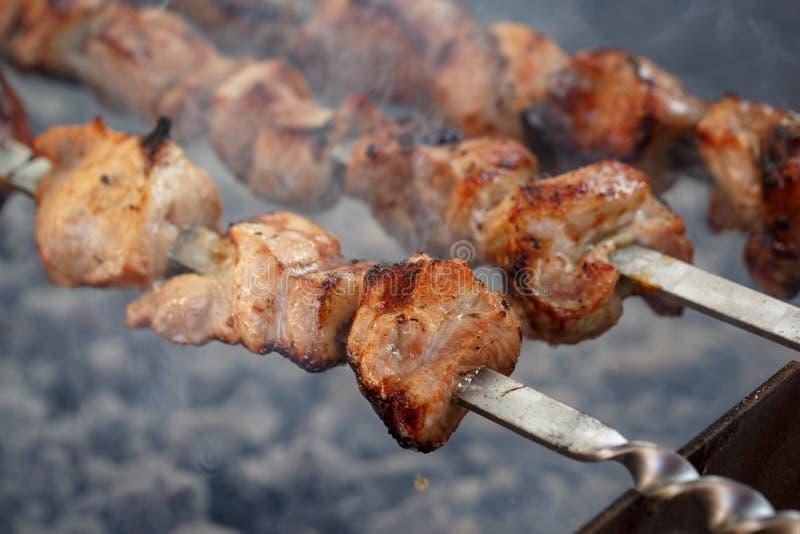 Ψημένος στις juicy εύγευστες φέτες χοιρινού κρέατος ξυλάνθρακα που τίθενται στα οβελίδια στοκ φωτογραφίες