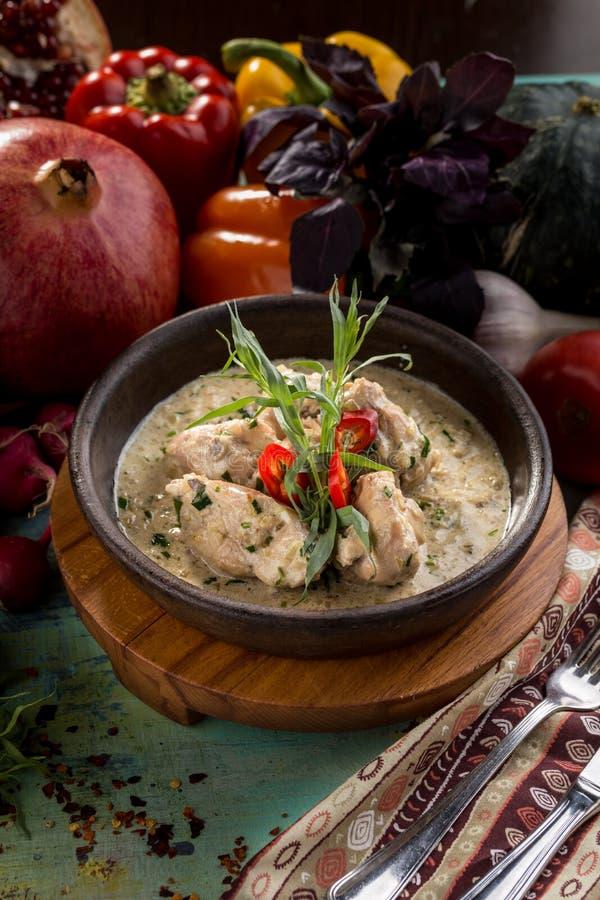 Ψημένο κοτόπουλο με τα ψημένα στη σχάρα λαχανικά, τα πράσινα και την άσπρη σάλτσα στο τηγάνι στον ξύλινο πίνακα στοκ φωτογραφία