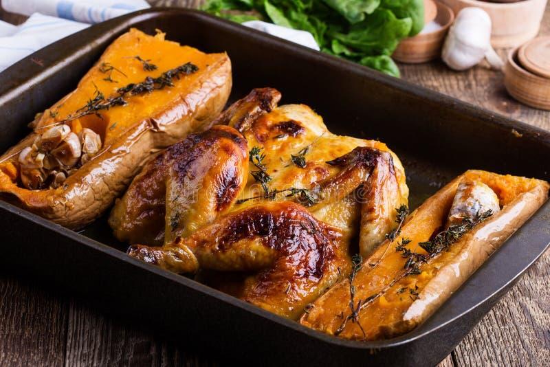 Ψημένο κοτόπουλο με την εποχιακή κολοκύνθη, το σκόρδο και τα χορτάρια φθινοπώρου butternut στοκ εικόνα