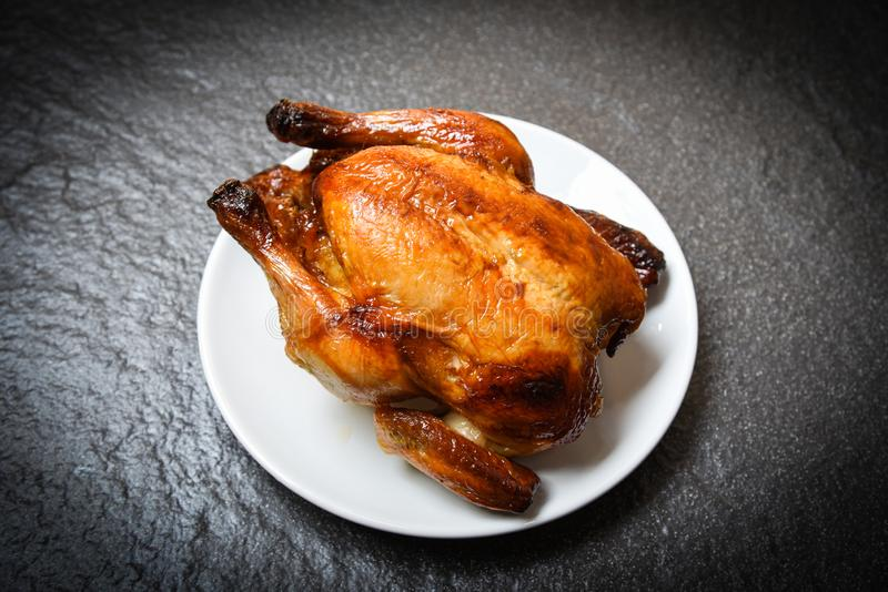 Ψημένο κοτόπουλο - ψημένο ολόκληρο κοτόπουλο που ψήνεται στη σχάρα στο άσπρο πιάτο και το σκοτεινό υπόβαθρο στη τοπ άποψη στοκ εικόνα με δικαίωμα ελεύθερης χρήσης