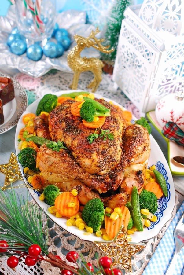 Ψημένο κοτόπουλο με τα λαχανικά στον πίνακα Χριστουγέννων στοκ φωτογραφία