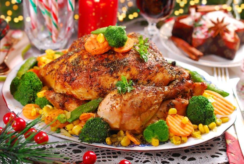 Ψημένο ολόκληρο κοτόπουλο με τα λαχανικά στον πίνακα Χριστουγέννων στοκ εικόνες