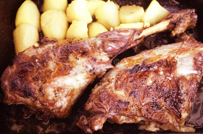Ψημένο πόδι αρνιών με τα μεσογειακά καρυκεύματα και τις ψημένες πατάτες στο τηγάνι στοκ εικόνα με δικαίωμα ελεύθερης χρήσης