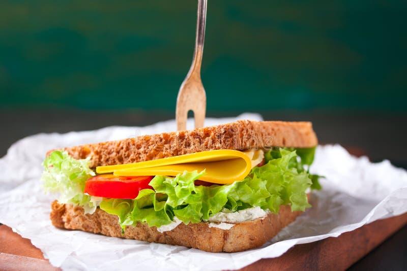 Ψημένο σάντουιτς με τα φύλλα, τις ντομάτες και το τυρί σαλάτας με το δίκρανο σε έναν τέμνοντα πίνακα στοκ εικόνες