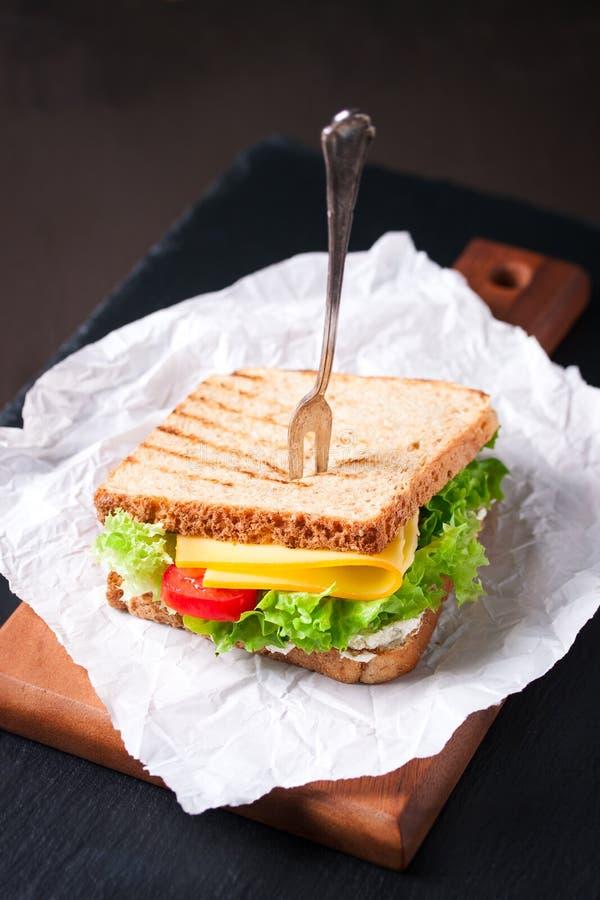 Ψημένο σάντουιτς με τα φύλλα, τις ντομάτες και το τυρί σαλάτας με το δίκρανο σε έναν τέμνοντα πίνακα στοκ φωτογραφία