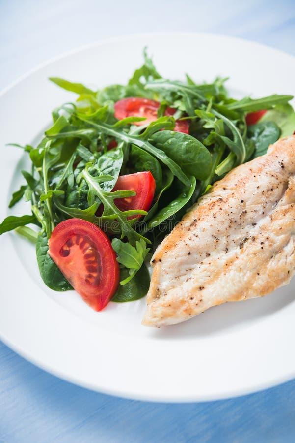 Ψημένο στήθος κοτόπουλου και φρέσκια σαλάτα με την ντομάτα και τα πράσινα & x28 σπανάκι, arugula& x29  κλείστε επάνω στο μπλε ξύλ στοκ εικόνες με δικαίωμα ελεύθερης χρήσης