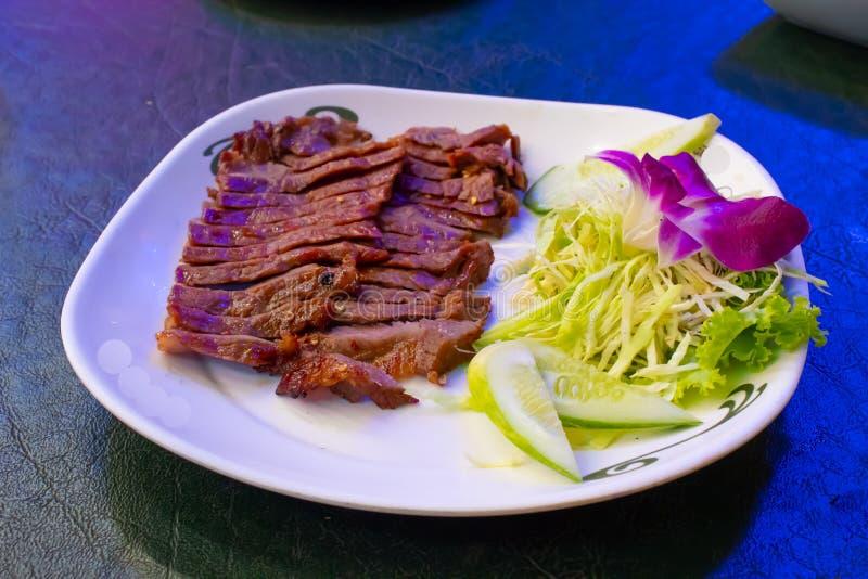 Ψημένο στη σχάρα βόειο κρέας σε ένα άσπρο πιάτο με τη σάλτσα και τα λαχανικά στοκ φωτογραφίες
