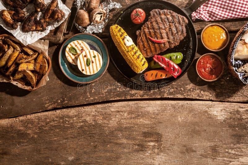 Ψημένο στη σχάρα γεύμα που διαδίδεται έξω στον αγροτικό ξύλινο πίνακα στοκ εικόνες