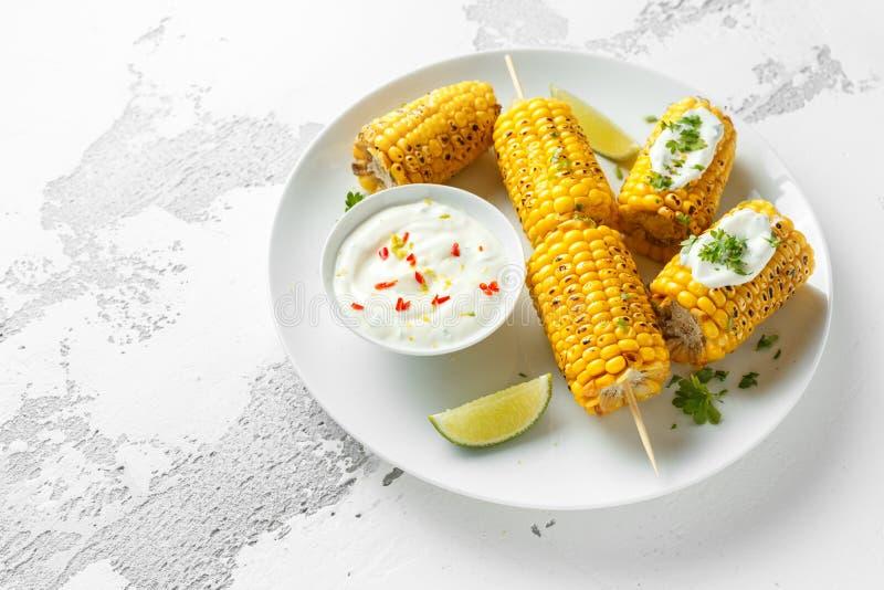 Ψημένο στη σχάρα γλυκό καλαμπόκι με την άσπρους μεξικάνικους σάλτσα, τα τσίλι και τον ασβέστη Υγιή θερινά τρόφιμα στοκ φωτογραφία με δικαίωμα ελεύθερης χρήσης