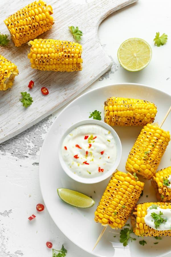 Ψημένο στη σχάρα γλυκό καλαμπόκι με την άσπρους μεξικάνικους σάλτσα, τα τσίλι και τον ασβέστη Υγιή θερινά τρόφιμα στοκ εικόνες