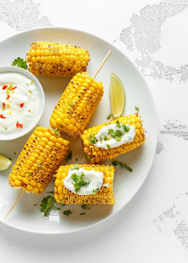 Ψημένο στη σχάρα γλυκό καλαμπόκι με την άσπρους μεξικάνικους σάλτσα, τα τσίλι και τον ασβέστη Υγιή θερινά τρόφιμα στοκ φωτογραφία