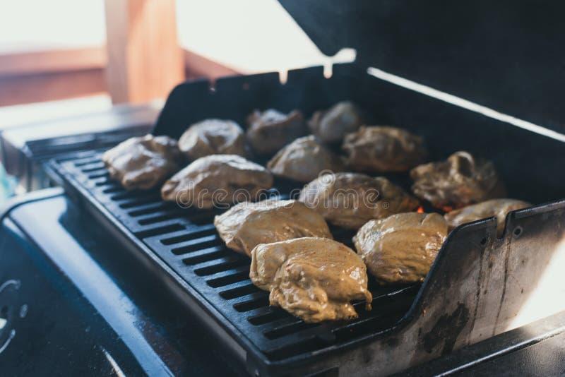 ψημένο στη σχάρα κοτόπουλο σε ένα πικ-νίκ Το άτομο έβαλε το κοτόπουλο στο μαρινάρισμα στη σχάρα για την προετοιμασία του Ολόκληρα στοκ εικόνα