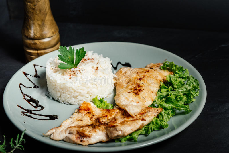 Ψημένο στη σχάρα κοτόπουλο με το risotto και μαϊντανός που εξυπηρετείται στο bistro στοκ εικόνα με δικαίωμα ελεύθερης χρήσης