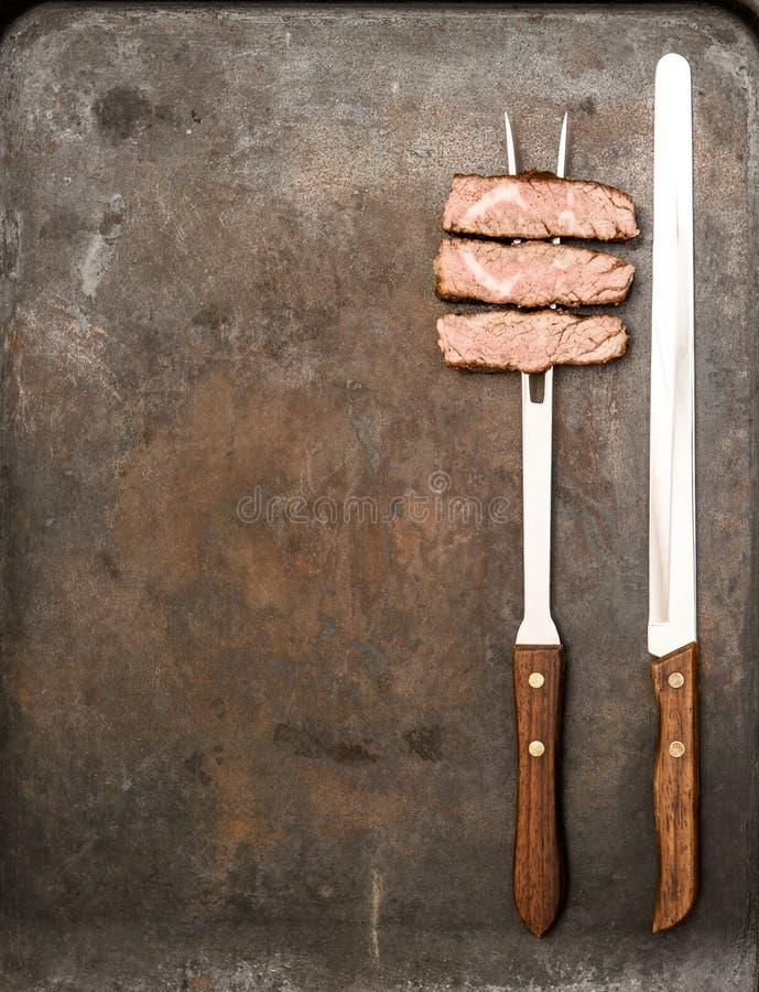 Ψημένο στη σχάρα κρέας βόειου κρέατος με το δίκρανο και το μαχαίρι τρόφιμα μπουλεττών ανασκόπησης πολύ κρέας πολύ στοκ φωτογραφίες με δικαίωμα ελεύθερης χρήσης