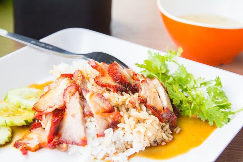 Ψημένο στη σχάρα κόκκινο χοιρινό κρέας στη γλυκιά σάλτσα με το ρύζι και αγγούρι στον πίνακα στοκ εικόνα