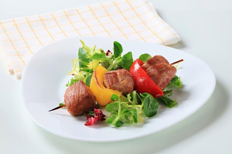 Ψημένο στη σχάρα οβελίδιο χοιρινού κρέατος με τα πράσινα σαλάτας στοκ φωτογραφία με δικαίωμα ελεύθερης χρήσης