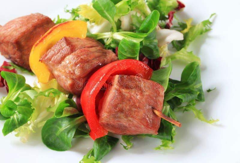 Ψημένο στη σχάρα οβελίδιο χοιρινού κρέατος με τα πράσινα σαλάτας στοκ εικόνα