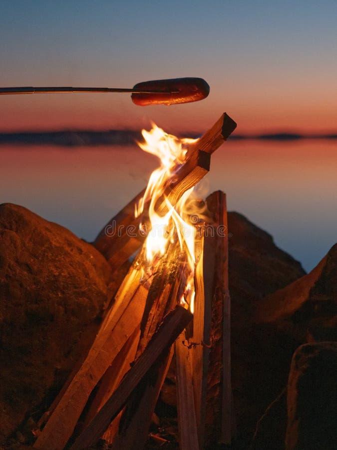 Ψημένο στη σχάρα λουκάνικο στην πυρά προσκόπων στοκ εικόνες