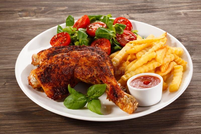 Ψημένο στη σχάρα πόδι κοτόπουλου με τα τσιπ και τα λαχανικά στοκ εικόνα με δικαίωμα ελεύθερης χρήσης