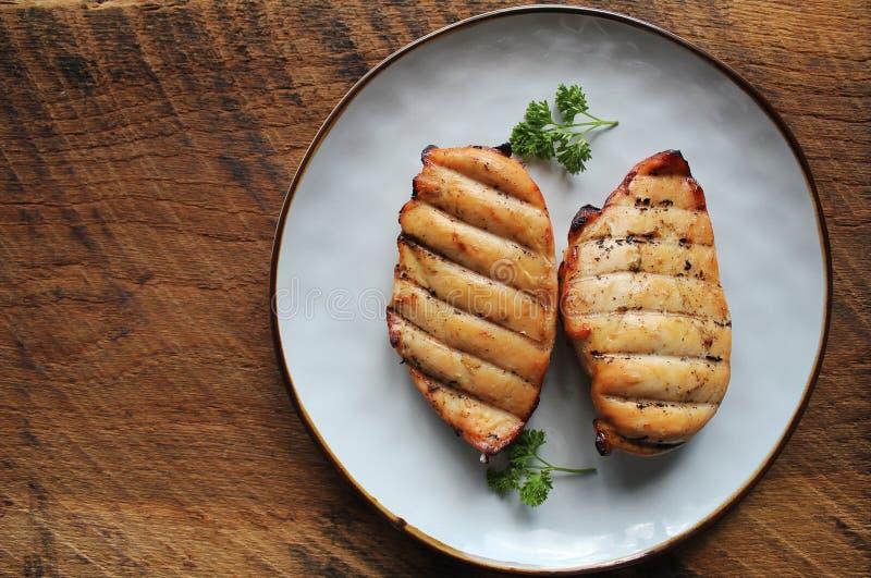 Ψημένο στη σχάρα στήθος κοτόπουλου στο σκοτεινό ξύλινο υπόβαθρο στοκ εικόνες με δικαίωμα ελεύθερης χρήσης