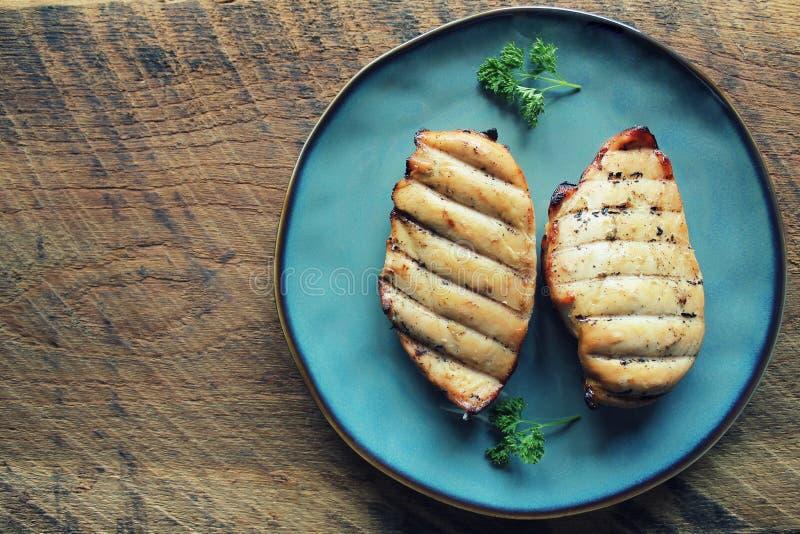 Ψημένο στη σχάρα στήθος κοτόπουλου στο σκοτεινό ξύλινο υπόβαθρο στοκ εικόνα