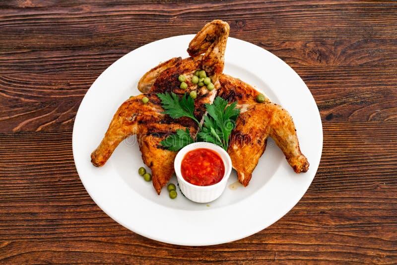 Ψημένο στη σχάρα τηγανισμένο κοτόπουλο Tabaka σε ένα πιάτο σε ένα ξύλινο υπόβαθρο, τοπ άποψη ψητού στοκ εικόνες με δικαίωμα ελεύθερης χρήσης