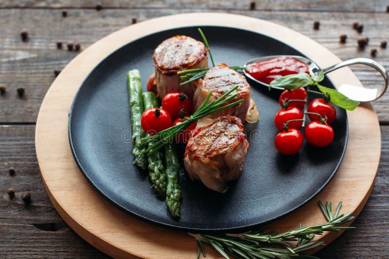 Ψημένο στη σχάρα χοιρινό κρέας με τα λαχανικά στο μαύρο πιάτο στοκ φωτογραφία με δικαίωμα ελεύθερης χρήσης