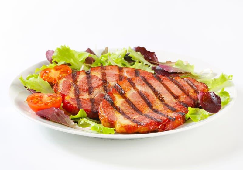 Ψημένο στη σχάρα χοιρινό κρέας με τα πράσινα σαλάτας στοκ εικόνα με δικαίωμα ελεύθερης χρήσης