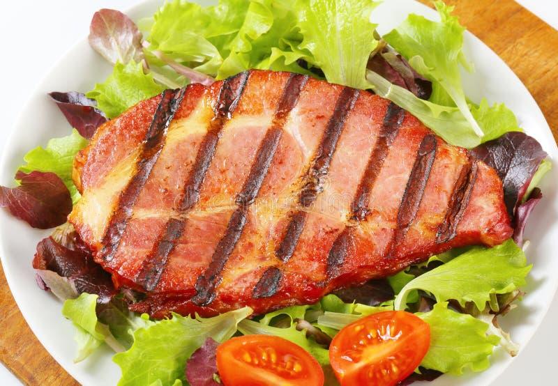 Ψημένο στη σχάρα χοιρινό κρέας με τα πράσινα σαλάτας στοκ εικόνα