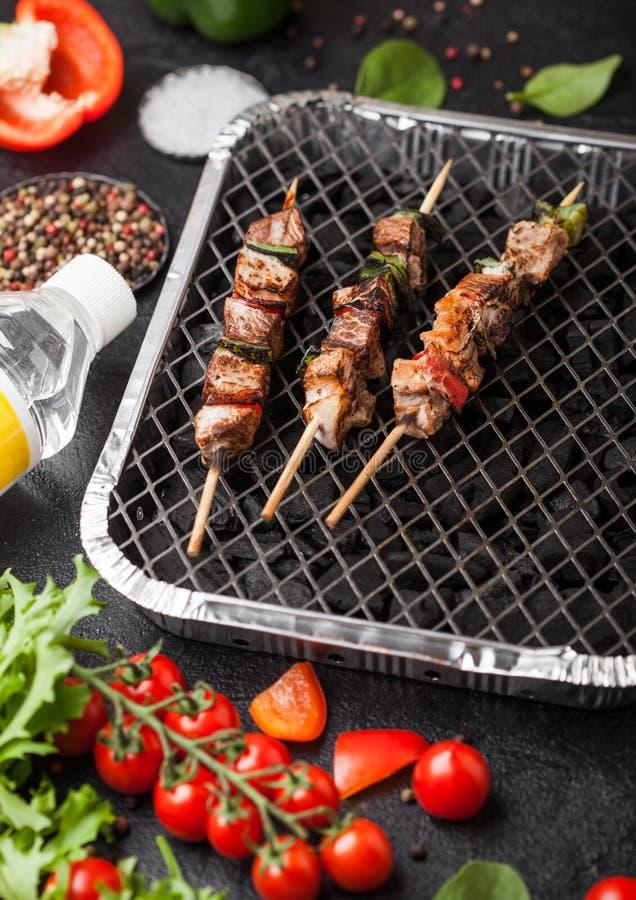 Ψημένο στη σχάρα χοιρινό κρέας kebab με την πάπρικα στη μίας χρήσης bbq άνθρακα σχάρα με τα φρέσκα λαχανικά στο blackbackground Α στοκ φωτογραφία