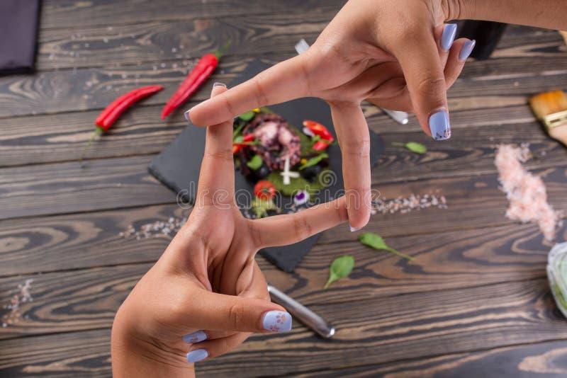 Ψημένο στη σχάρα χταπόδι με τα λαχανικά στον πίνακα μαύρου σχιστόλιθου Νόστιμα θαλασσινά στην πλάκα στον ξύλινο πίνακα χέρι-πλαίσ στοκ εικόνα