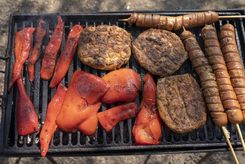 Ψημένο στη σχάρα Burgers, λουκάνικο χοτ-ντογκ και κόκκινα πιπέρια σε μια σχάρα σχαρών στοκ φωτογραφία
