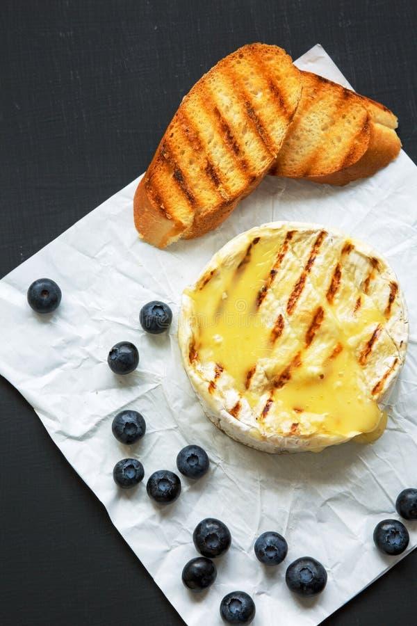 Ψημένο στη σχάρα camembert τυρί στο έγγραφο με τις φρυγανιές και τα βακκίνια στη σκοτεινή επιφάνεια Τρόφιμα για το κρασί Τοπ άποψ στοκ φωτογραφία με δικαίωμα ελεύθερης χρήσης