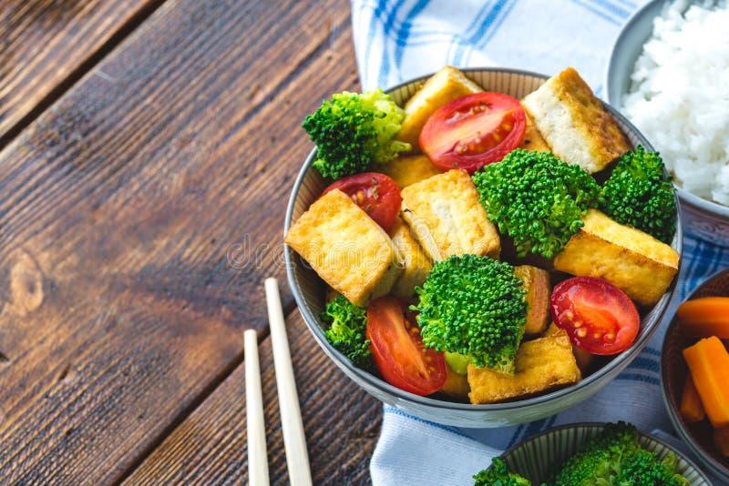 Ψημένο στη σχάρα tofu με το μπρόκολο και ντομάτες στο άσπρο κύπελλο στο τραπεζομάντιλο με chopsticks στη αριστερή πλευρά στοκ φωτογραφία με δικαίωμα ελεύθερης χρήσης