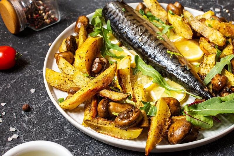 Ψητό σκουμπρί με λεμόνι, ψητές πατάτες και μανιτάρια σε ένα πιάτο στο μαύρο πέτρινο φόντο στοκ εικόνες