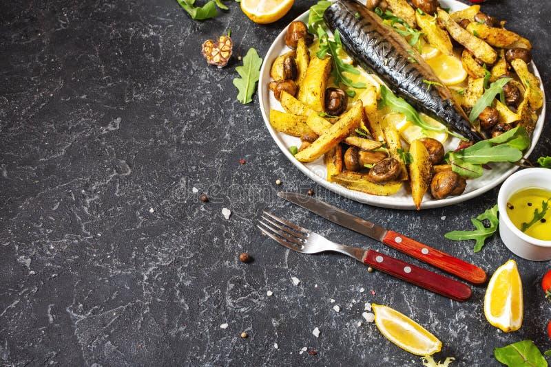 Ψητό σκουμπρί με λεμόνι, ψητές πατάτες και μανιτάρια σε ένα πιάτο στο μαύρο πέτρινο φόντο στοκ εικόνα