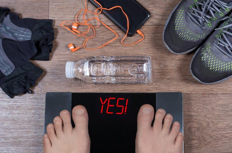 Ψηφιακές κλίμακες με τα αρσενικά πόδια σε τους και το σημάδι ναι! από τα gymshoes, αθλητικά γάντια, νερό στοκ φωτογραφία με δικαίωμα ελεύθερης χρήσης