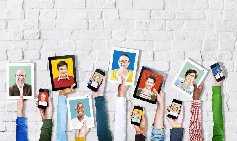 Ψηφιακές συσκευές εκμετάλλευσης χεριών με τα πρόσωπα των ανθρώπων στοκ φωτογραφία
