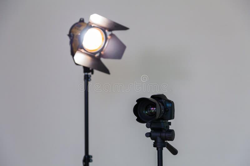 Ψηφιακή κάμερα SLR και ένα επίκεντρο με έναν φακό Fresnel σε ένα γκρίζο υπόβαθρο Πυροβολισμός στο εσωτερικό στοκ φωτογραφία με δικαίωμα ελεύθερης χρήσης