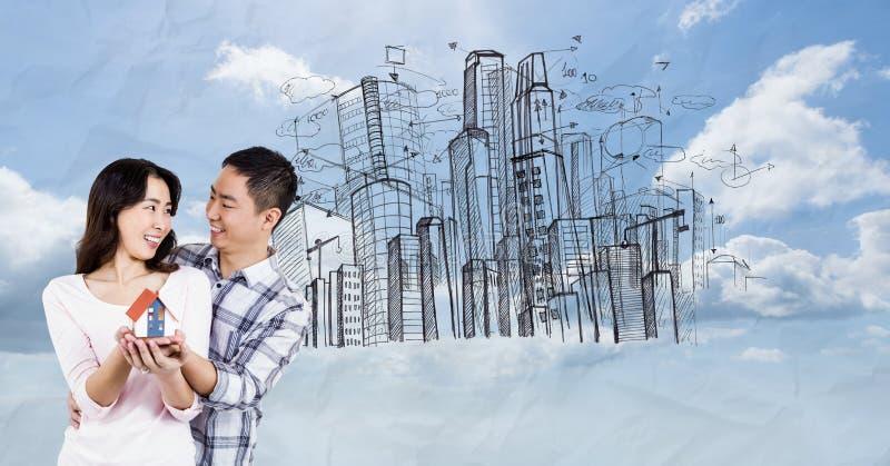 Ψηφιακή σύνθετη εικόνα του προτύπου σπιτιών εκμετάλλευσης ζευγών ενάντια στα κτήρια στον ουρανό στοκ φωτογραφία