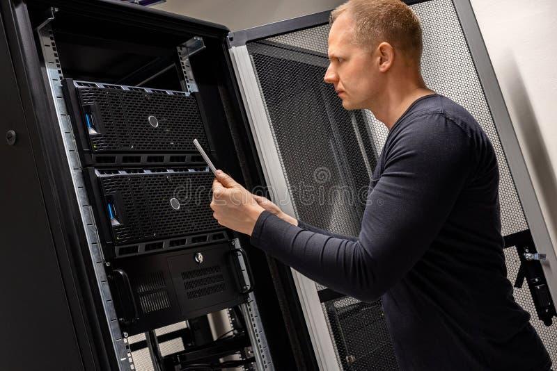 Ψηφιακή ταμπλέτα εκμετάλλευσης υποστήριξης ΤΠ που αναλύει τους κεντρικούς υπολογιστές και το δίκτυο σε Datacenter στοκ εικόνα με δικαίωμα ελεύθερης χρήσης