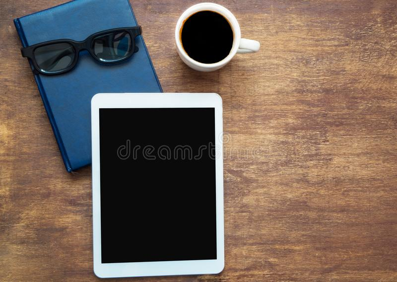 Ψηφιακή ταμπλέτα με το μαύρο κενό διάστημα στην οθόνη και το φλιτζάνι του καφέ, διάστημα αντιγράφων Κλειστό μπλε σημειωματάριο με στοκ εικόνα