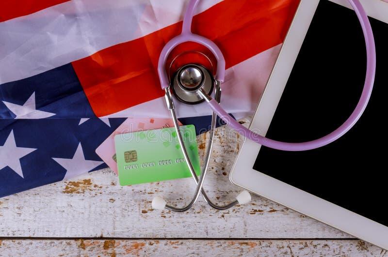 Ψηφιακή ταμπλέτα στο στηθοσκόπιο πιστωτικών καρτών στην αμερικανική εθνική σημαία στοκ φωτογραφία με δικαίωμα ελεύθερης χρήσης