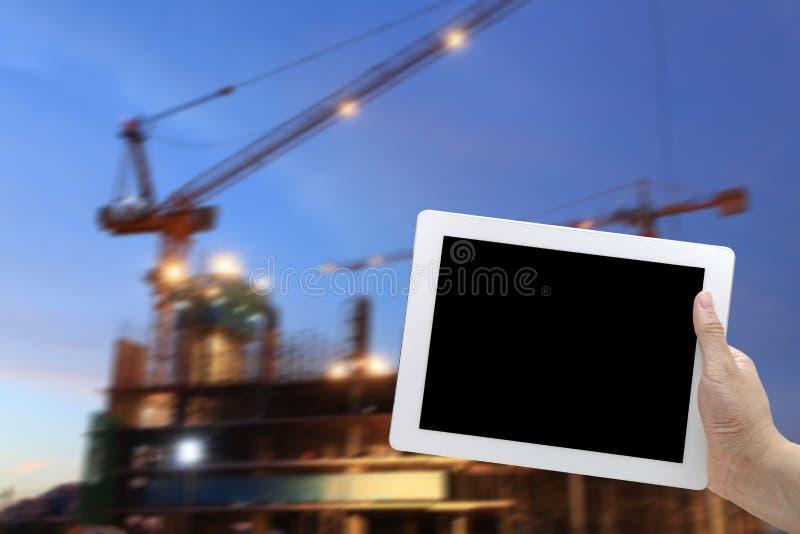 Ψηφιακό εργοτάξιο οικοδομής ταμπλετών λαβής χεριών στο υπόβαθρο σούρουπου στοκ φωτογραφία με δικαίωμα ελεύθερης χρήσης